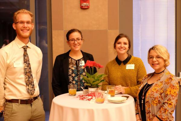 Young Alumni around a table at an in person OSU hosted event