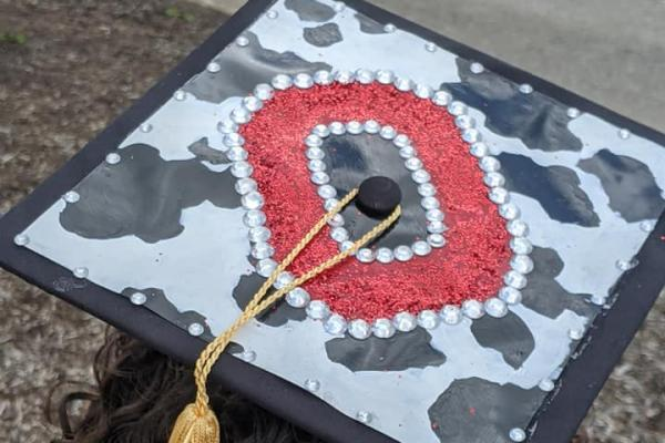Graduation cap with holstein spots and a red Block O in the center.