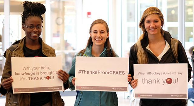 Students holding thank you signs in appreciation of scholarship donors