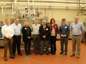 A team of corporate partners standing together in front of some of the donated pilot plant equipment.