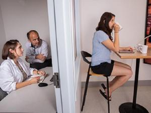 Scientists observe as woman sips coffee in the Sensory Lab