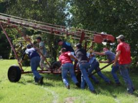 ASM Club members teamed up to push a hay elevator from a field to a barn.