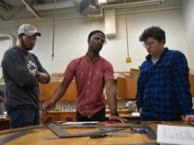 Manny Barnes (center) working with classmates on a team project.