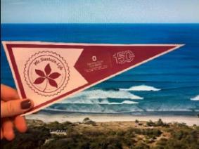 CFAES 150th anniversary pennant held on a beach.
